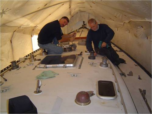 Mike & Mike stripping hardware and the winch farm on deck.  The molded winch platforms on the cabin were cut off flush.