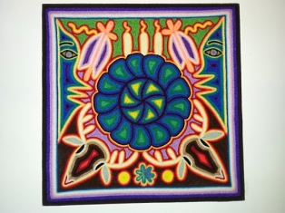 A Huichol painting made out of very fine colored threads. You can see the two sides of the Goddess of the Sea's face among many significant symbols unique to the Huichols.