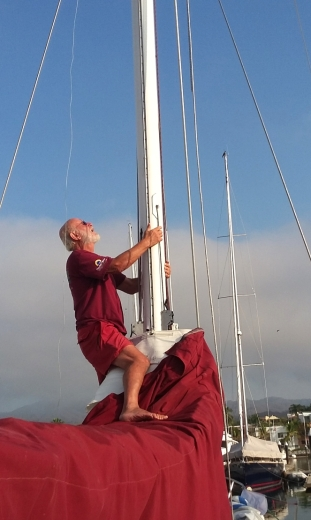 "Mike from the s/v Honu, helping me fish a new jib haulyard down the mast. On day one of the regatta, the jib haulyard broke as the crack foredeck crew was tightening it for the final leg to the finish. Didn't help our placement in the race as ""old whitie"" slid into the drink. But Pat & Anne got him (our #1 jib) aboard quickly and the #3 to get us to the line."