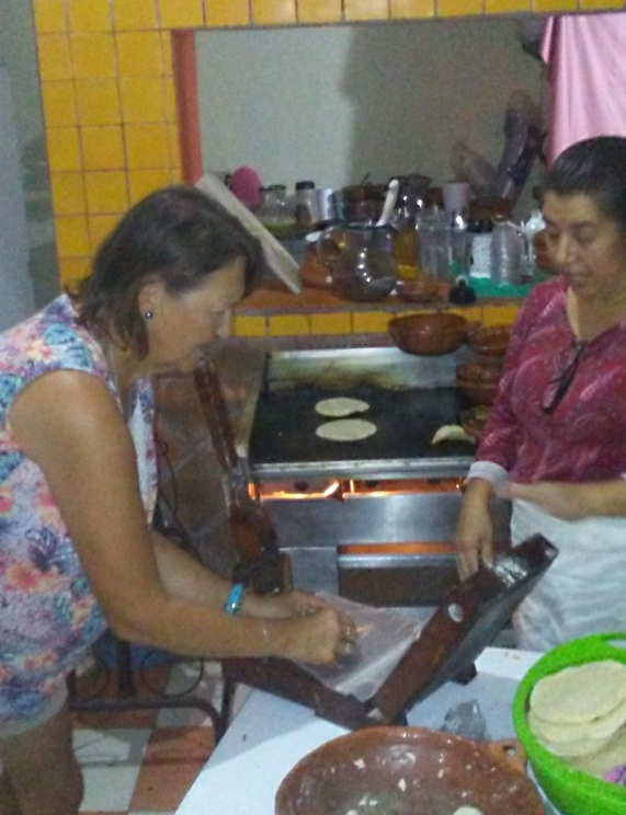 Coqui is teaching Donna the cool way to make tortillas in the kitchen of her restaurant. It's all in the wrist.