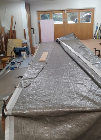 We needed a new primary jib. Resurrecting this long ago retired #2 became the best option. I used contact cement to glue long strips of Pentex fabric cut from an old mainsail to reinforce the failing leach of the sail.